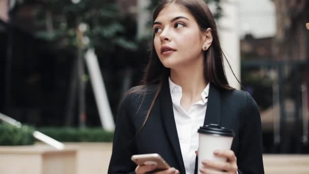 Professional young businesswoman walking on urban street using smartphone and drink coffee. Concept: new business, communication, banker. Outside, slow motion