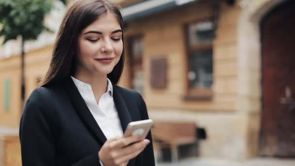 Young beautiful business woman using smartphone and walking on the old street. She surfing the internet. Concept: new business, communication, banker, manager