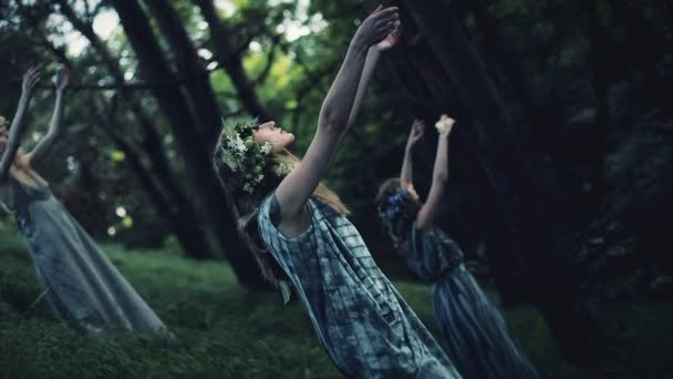 Mystical girls in the woods hold a ritual.They are dressed in long dresses with wreath on the head. Witches, esoteric sessions, magic, divination, otherworldly forces
