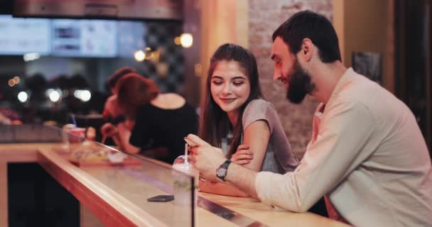 Attractive young couple using smartphone at cafe late in the evening. Friends, communication, couple, dating, chat conception