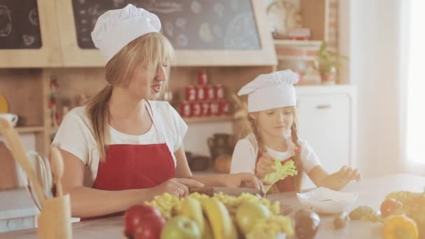 Mom and little daughter cook in the kitchen: they make a fresh garden salad, and mother teaches the girl.Cooking and happy family concept