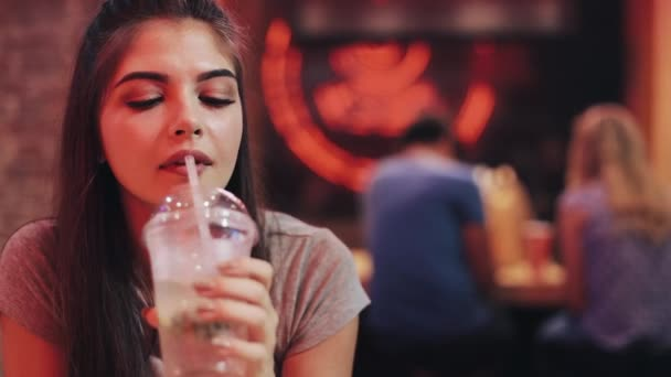 Young woman sitting in bar, drinking lemanade and looking into the camera. Woman enjoying night-life while communicating with friends on her smartphone
