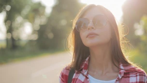 Mladá krásná žena stopování stojící na vozovce nikde znamení. Letní čas