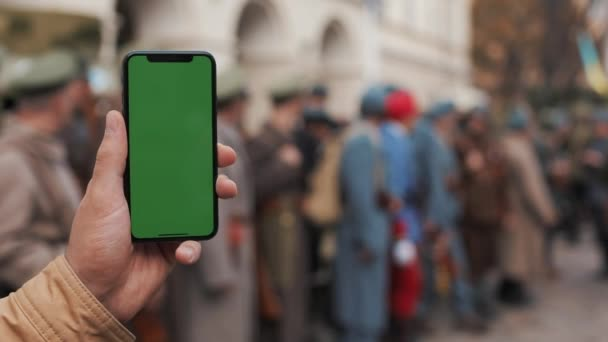 Closeup of a mans hand holding a mobile telephone with a vertical green screen on the streets. Big screen. Military soldiers in the background