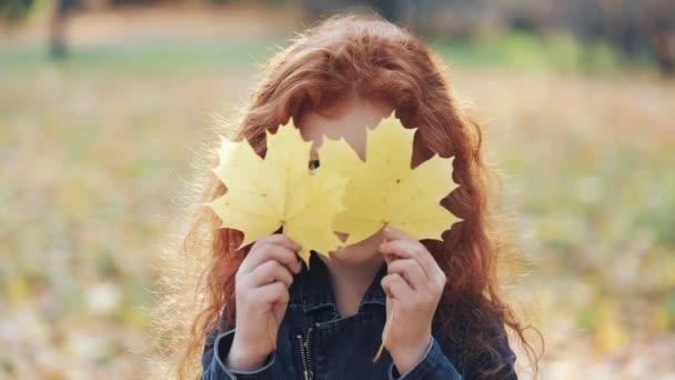 Portrét roztomilá holčička zrzka, usmíval se skrývá její oči žluté listy. Roztomilé dítě skrývá přes žluté listy. Podzimní čas