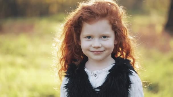 Portrait of cute redhead little girl in an autumn park. Slow motion. Autumn Park. Young little girl is smiling at the camera