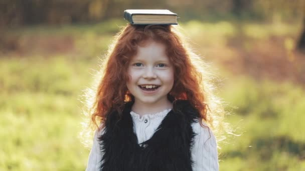 Smiling little redhead girl holding book on head and looking into the camera standing in autumn park. Slow motion