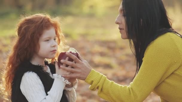 A happy mother and cute little daughter sitting together and playing with apple in a city park on a picnic. Autumn time