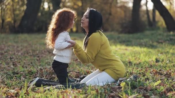 Máma a dcera hraje v podzimním parku, budou jíst a smíchu. pomalý pohyb
