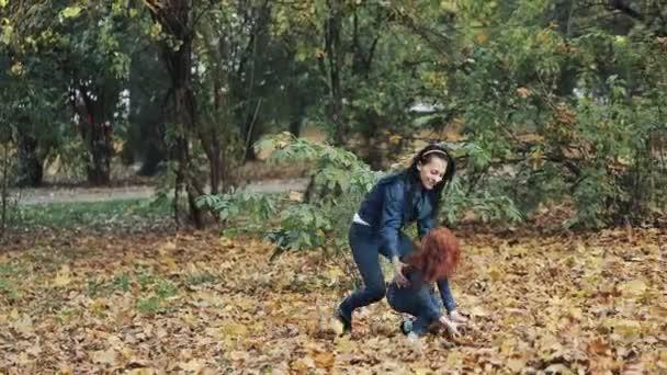 glückliche Mutter und ihre kleine Tochter haben Spaß im Herbstpark. junge Familie wirft Blätter und lacht. Zeitlupe
