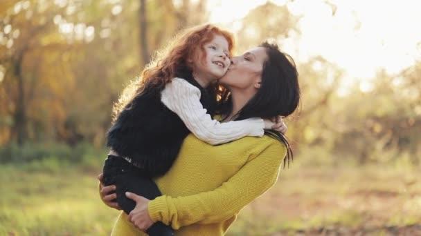 Krásné máma a její sladká dcera chodí v podzimním parku. Maminka holdeng dceru v náručí. Smáli se, hovoří a bavit