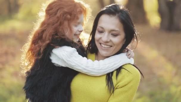 eine schöne Mutter und ihre süße Tochter spazieren im herbstlichen Park. Mutter hält ihre Tochter auf dem Arm. sie lachen, reden und haben Spaß