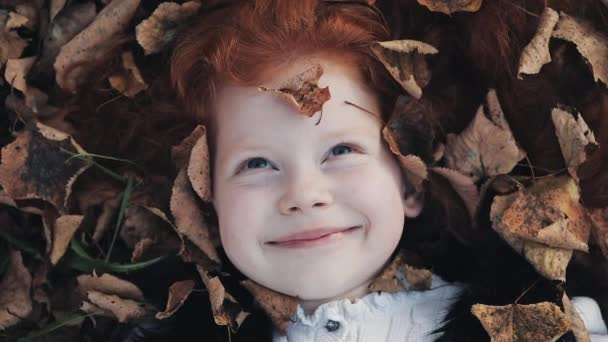A little cute redhead girl lies on a yellow leafs in the autumn park. She looking intot the camera and smiling. leaves falling slowly, top view