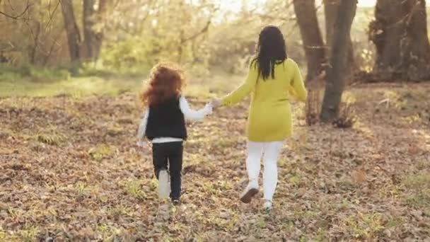 Happy young mother and her little redhead daughter runing together in an autumn park. They laughing and having fun holding hands. Slow motion