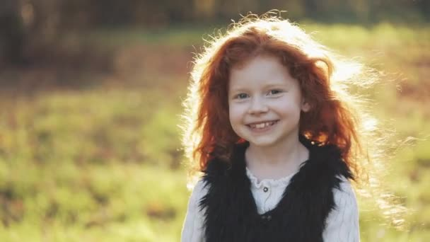 Portrait of cute redhead little girl walking in an autumn park. Slow motion. Autumn Park. Young little girl is smiling into the camera