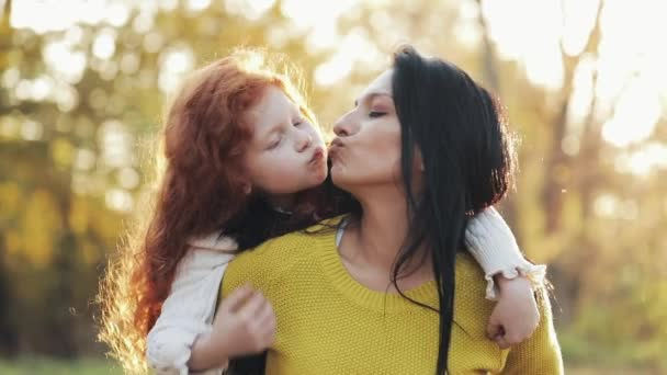 Happy young mother and her little redhead daughter having Fun in an autumn park. They playing, hugging and laughing. Slow motion