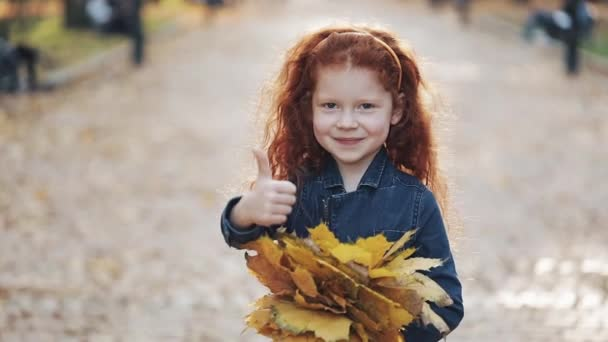 Cute little redhead daughter standing in autumn park and looking into the camera. She holding ha yellow leaves in her hands and showing a thumb up gesture