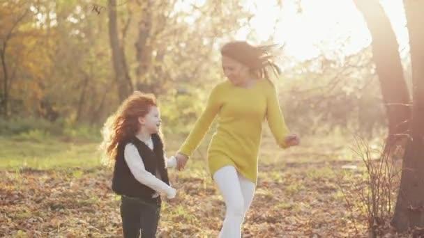 Šťastná mladá matka a její malý rusovláska dcera runing společně v podzimním parku. Se směje a Bavíte se drží za ruce. Zpomalený pohyb