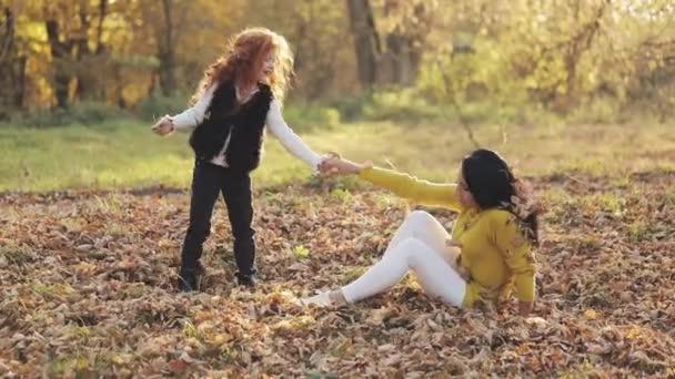 Šťastná Maminka a její malá dcera zrzka baví v podzimním parku. Oni hrají, objímání a směje se. Zpomalený pohyb