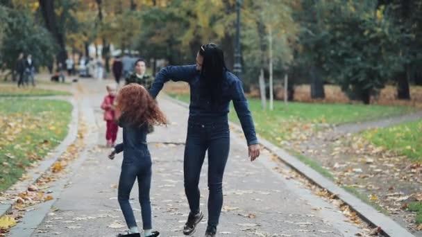 Šťastný matka a její malá dcera baví v podzimním parku. Mladé rodiny chůzi a směje se. Pomalý pohyb