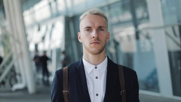 Serious Young Businessman with Backpack Standing Outside Airport and Looking into the Camera