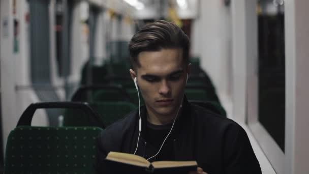 Mladý pohledný muž sedí na čtení knihy - dojíždění, student, znalosti koncepce veřejné dopravy. Mladý muž se sluchátky v tramvaji, čtení knihy.
