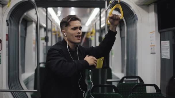 Fejhallgató hallgató-hoz zene és vicces tánc tömegközlekedési jóképű férfi portréja. Ő tartja a kapaszkodó