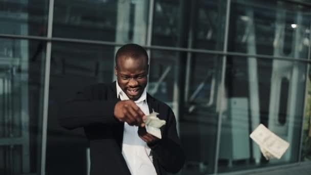 Mladý šťastný americký podnikatel bodový dolarů na ulici. Peníze déšť, padající dolarů. Nachází se poblíž centra office, zpomalené. Úspěšné podnikání