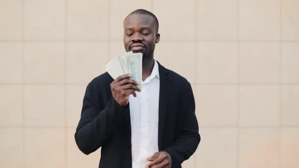 Portrét americký podnikatel stojící mimo poblíž kancelářská budova, předváděl své peníze. Podnikání, lidi, finance a snadné peníze koncepce