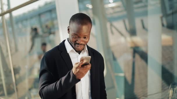 Happy african american businessman cheering celebrating looking at cell phone and holding a big amount of money in his hands. He stands in the street near the office center or bank