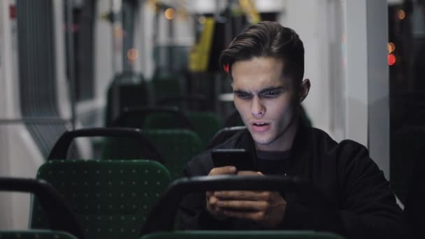 Unhappy young businessman with smartphone reading bad news riding in public transport