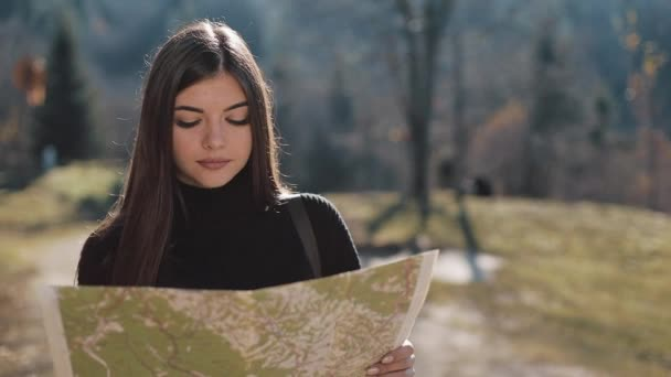 Young beautiful woman hiking on a mountain trail, stops and checks map for directions. Woman with old map in mountains