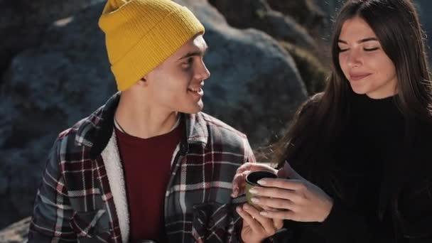 Paar in Liebe Tee trinken aus einem Becher Thermoskanne auf dem Hintergrund der Berge. Touristen sitzen auf Steinen und Blick auf die schöne Natur. Tourismus, Erholung, Urlaub, Natur, Wanderung Konzept