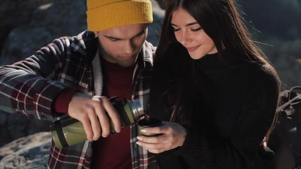 Verliebte Paare trinken Tee aus einem Becher Thermoskanne vor dem Hintergrund der Berge. Touristen sitzen auf Steinen und schauen auf die schöne Natur. Tourismus, Erholung, Urlaub, Natur, Wanderkonzept