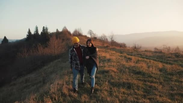 Couple in love hiking outdoors. Hikers man and woman trekking walking with backpacks in trail at sunset in mountains