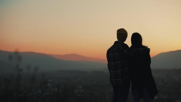 Sziluettjét a fiatal pár a szerelem élvezi a naplementét a hegyek fölött. Nyaralás, utazás, romantika, házasság javaslat fogalma