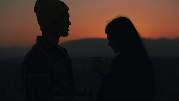 Silhouette of young couple in love drinking tea from a mug of thermos on the beautiful sunset background of mountains. Tourism, romantic date, rest, vacation, nature, hike concept