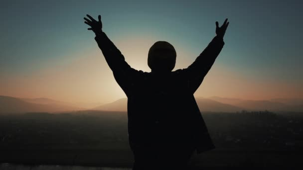 Silueta člověka vyvolává ruce vzhůru stojící na hoře na západ slunce. Koncept svobody