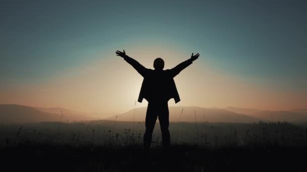 Die Silhouette des Menschen hebt die Hände, wenn er im Sonnenuntergang auf dem Berg steht. Freiheitskonzept