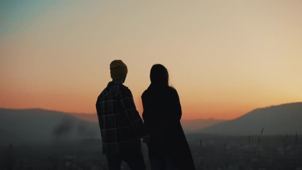 Silhouette of young couple in love enjoying a sunset over the mountains. Vacation, travel, romance, marriage proposal concept