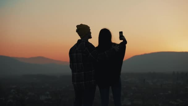 Silhouette of young couple in love enjoying a sunset over the mountains. They taking photo on smartphone. Vacation, travel concept