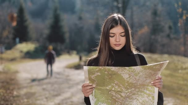 Travelling to the mountains. Young woman holds old map standing in the forest. The tourist travels in beautiful mountains