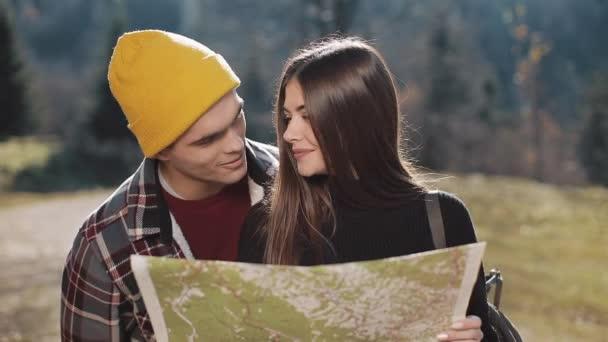 Mladý, usměvavý šťastný pár stojící v horách. Oni se těší jejich pěší turistiku. Při pohledu na turistické mapě. Snaží se najít směr. Zpomalený pohyb