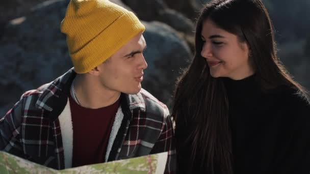 Travel to the mountains. Beautiful couple in love sits on the rock and learns a map. They talk with each other, laughing and having fun