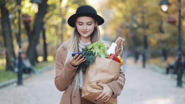 glückliche junge schöne Frau in elegantem Mantel, die durch den Park läuft und Produktpakete in der Hand hält und das Smartphone benutzt. sie blickt in die Kamera. Einkaufen, gesunde Ernährung, Internet-Shop-Konzept
