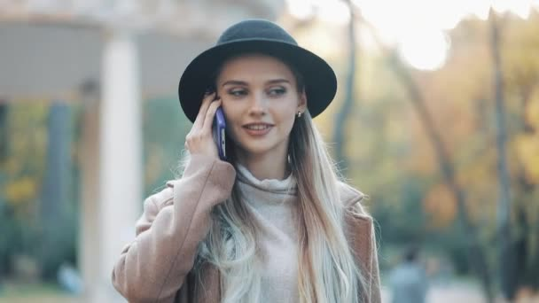 schöne attraktive Frau in Mantel und Hut telefoniert in der Innenstadt bei sonnigem Frühlingswetter