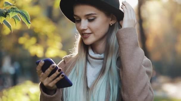 Eine junge Frau im Mantel mit Smartphone steht im Herbstpark. Mädchen blickt in die Kamera. Technologie im Freien. Sonnenlicht