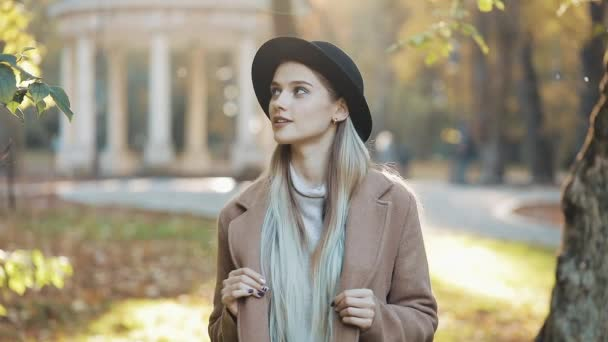 Amazing girl in coat with black hat standing down the park alley, looking into the camera and gives amazing smile. Park settings, trees, fallen leaves on the background