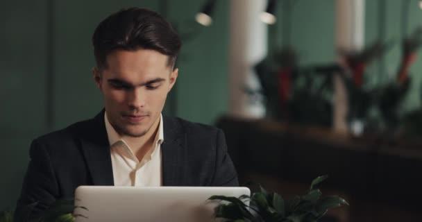 fröhliche junge Unternehmer sitzen in einem Café und arbeiten an einem Laptop. Gewinner schaut auf Laptop zeigt ja Geste, feiert Erfolg, gute Nachrichten im Web, genießen Triumph, tat es