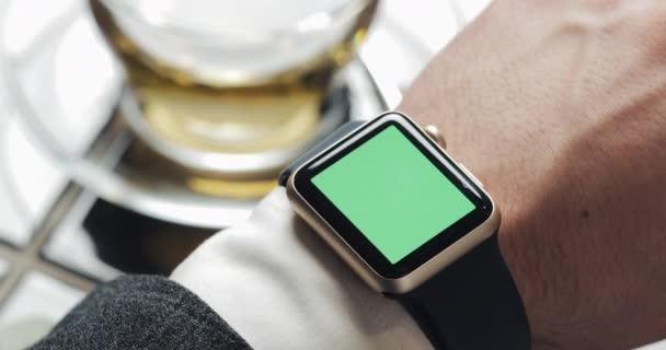 Nahaufnahme von Geschäftsmannhänden mit Smartwatch Green Screen Chroma Key. gemütliches Café im Hintergrund